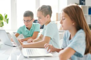 Three young schoolkids in casualwear sitting in computer classroom